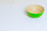 Bamboo green plate on white wooden table, side view, copyspace