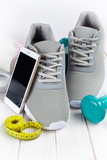Smartphone, earphones, sport shoes, dumbbells and measuring tape on wooden board