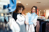 Two young girls look at clothing in store - 229413357