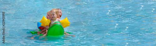 Leinwanddruck Bild Drei Kleinkinder mit Riesenspaß auf einem Schwimmkrokodil im Schwimmbad