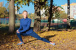 Beautiful sporty woman does sport exersices in the park, outdoors, soft focus background