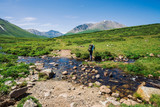 Man with large backpack crosses mountain creek over stones. Tourist goes on path in green valley to wonderful snowy mountains. Hiking in highlands. Amazing atmospheric landscape of majestic nature.