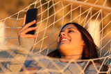 Happy girl resting on a hammock using a smart phone - 229452533