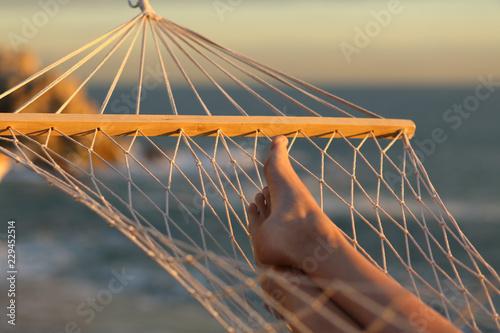 Leinwanddruck Bild Woman legs resting on a hammock on vacation
