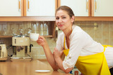Mature woman holding cup of coffee in kitchen. - 229455330
