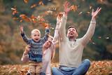 Happy family in autumn park - 229456345