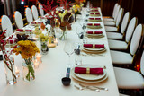 table setting in a restaurant decorated with napkins on plates and flowers and candles - 229460348