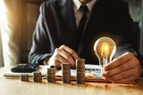 business man hand holding lightbulb with using smartphone and calculator to calculate and money stack. idea saving energy and accounting finance in morning light  - 229488944