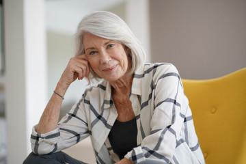 Stylish senior woman sitting casually indoors and smiling
