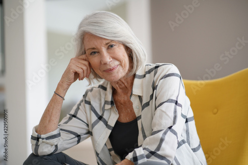 Stylish senior woman sitting casually indoors and smiling
