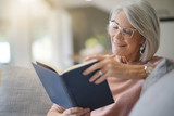Senior woman reading on couch at home - 229502341