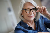 Attractive senior woman at home with eyeglasses - 229502347