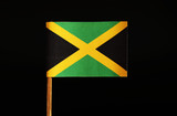 A official and original Flag of Jamaica on toothpick and on black background. Jamaica located in the central america.