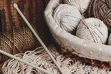 Needlework, macrame, knitting. Yarn and thread of natural colors in a wicker basket. Women's hobby. - 229517956