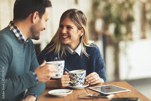 Leinwanddruck Bild Happy young couple on date in coffee shop