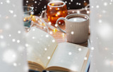 christmas, hygge and winter concept - book and cup of coffee or hot chocolate on table over snow