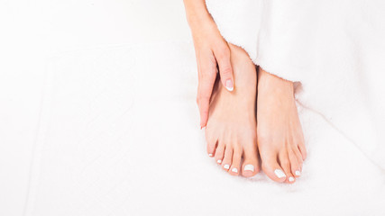 Female feet on towel. Nails getting a fresh and accurate look during a pedicure procedure © Stavros