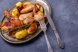 Roasted chicken on plate with cutlery - 229535187