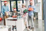 happy young start up team in santa hats holding christmas presents at workplace - 229543969
