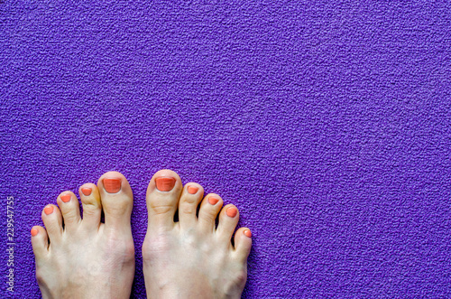 Leinwanddruck Bild Woman's feet on yoga mat. Top view