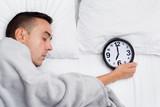 man in bed grabbing a clock at seven