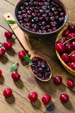 Cherry jam and red cherries in a basket on a wooden table.