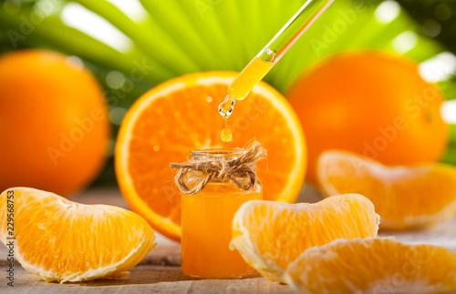 Leinwanddruck Bild Orange Essential Oil on green leaves background