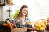 Healthy young woman eating salad in the kitchen - 229572157