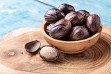 Whole nutmeg nuts in a bowl on blue rustic wooden table. - 229579188