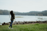 woman walking on a lake side in countryside - 229584923
