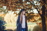 Beautiful happy girl with long hair, wearing stylish hat, coat posing in autumn park. Outdoor portrait, day light. - 229596326