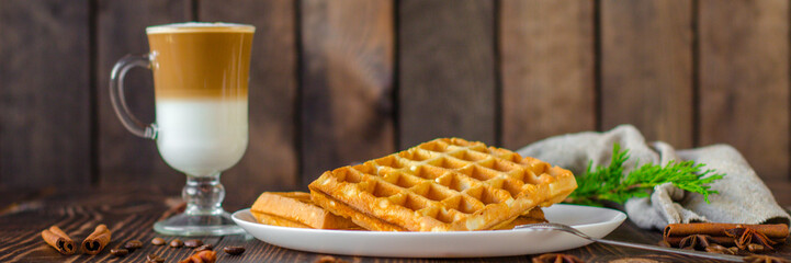 fresh belgian waffles, tasty jam and latte coffee on a wooden background. top view. © Alesia Berlezova