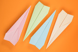 Colored paper planes on orange - 229616709
