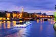 Pont Neuf and Cite island over Seine river with floating boat at night, France