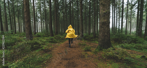 Leinwanddruck Bild man in yellow rain jacket runs in the forest, fog, rain and mist