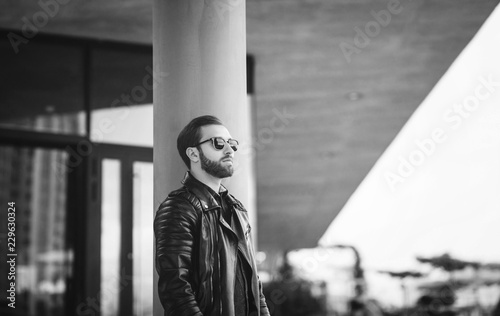 black and white portrait of a stylish man in a leather jacket on the street
