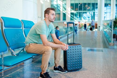 Leinwanddruck Bild Young man in an airport lounge waiting for flight aircraft.