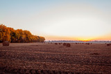 View of autumn field with haystacks at sunset. Ukrainian landscape