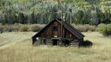 Dolly zoom of cabin in field with mountains in background - 229653323