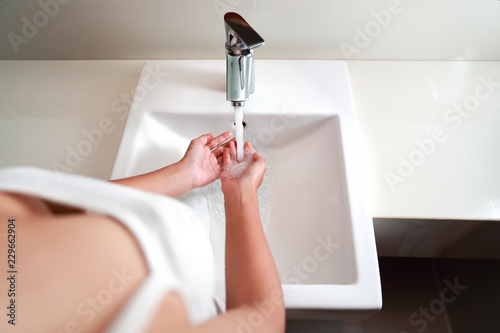 portrait of beautiful woman washing hands in bathroom - 229662904