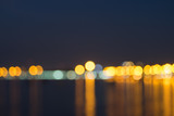 Colorful night bokeh light at the sea with city skyline defocused background. - 229692951
