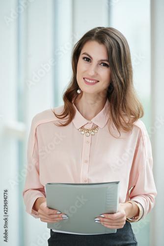 Uśmiechnięta piękna biznesowej kobiety mienia falcówka z znacząco dokumentami
