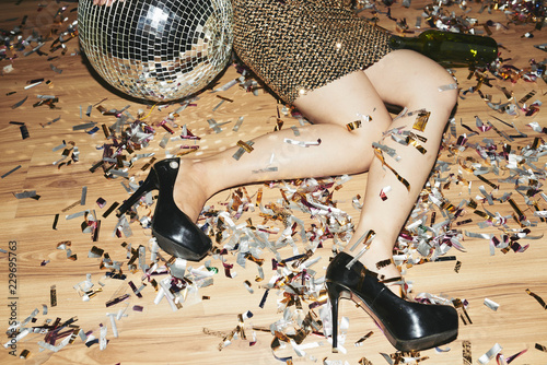 Foto Murales Cropped image of young woman in high heels and mini dress lying on the floor covered with confetti