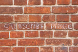 Text subscribe please on old vintage brick wall texture