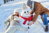 Familie baut einen Schneemann zusammen - 229701781