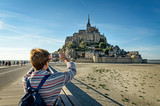 A tourist takes photos of Mont Saint Michel with her smartphone - 229701948