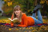 Teenage girl reading a book in autumnal park - 229705332