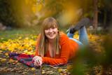 Happy teenage girl portrait in autumnal scenery - 229705365