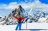 Man skiing on fresh powder snow. Ski in winter season, mountains and ski touring backcountry equipments on the top of snowy mountains in sunny day with Matterhorn in background, Zermatt in Swiss Alps. - 229706318