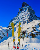 Ski in winter season, mountains and ski touring backcountry equipments on the top of snowy mountains in sunny day with Matterhorn in background, Zermatt in Swiss Alps. - 229706735